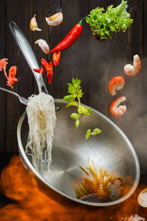Flying wok ingredients - shrimp, vegetables, lettuce, soy sauce and spices. Close-up, the process of cooking shrimp noodles. Chinese cuisine or recipes for oriental dishes cooked over an open fire