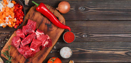 Ingredients for making goulash or stew, stew or gyuvech: top view of raw beef meat, herbs, spices, paprika, vegetables on a dark wooden background. Space for text, composition for flat lay
