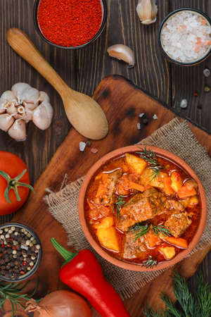 Beef stew with potatoes, carrots, wig and spices (Hungarian goulash) in a clay bowl, top view. Traditional dish of eastern europe and turkey - gyuvech, layout on a wooden table