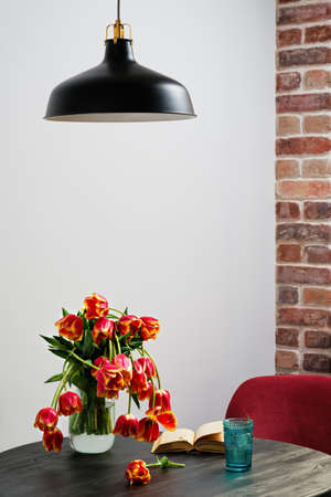 Vase of red slowly fading tulips in a modern living room - home decor, selective focus