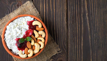 Crumbly fresh cottage cheese with sour cream, cranberry jam and nuts in a traditional clay bowl on a wooden background. Healthy breakfast made from curd, top view with copy space