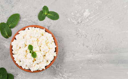 Homemade natural cottage cheese in a clay bowl on a gray neutral background, top view with copy space. Soft curd natural healthy food, wholesome diet food