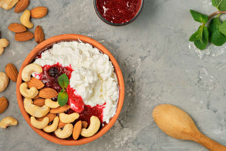 Fresh cottage cheese with sour cream, cranberry jam and nuts in traditional clay bowl. Neutral gray background. Healthy breakfast made from curd, top view with copy space