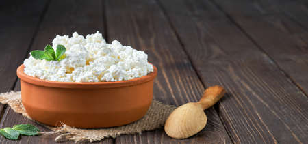 Farmer's cottage cheese in a traditional clay bowl, next to a wooden spoon, a dark wooden background. Close-up, selective focus. Soft curd natural healthy food, wholesome diet food