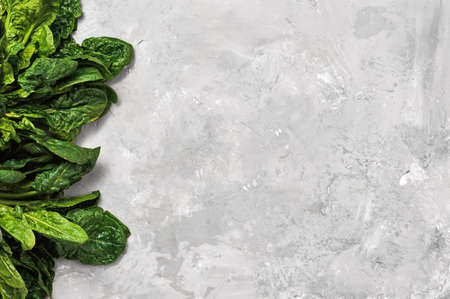 Green fresh spinach leaves on a neutral gray background. Top view with copy space for text. Healthy detoxification vegan diet concept Stock fotó