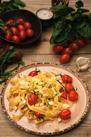 Pasta with grilled cheese slices, frying cherry tomatoes and olive oil. Selective focus, vertical frame. Ingredients for spaghetti on a wooden table. Vegetarian pasta idea