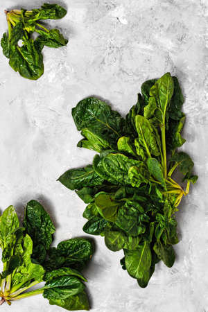 Green fresh spinach leaves on a neutral gray concrete background. Flat lay of freshly cut spinach lettuce. Healthy detoxification vegan diet concept. Banner idea Stock fotó