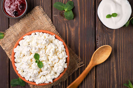 Natural cottage cheese in a traditional clay bowl, next to a wooden spoon, cranberry jam and sour cream in bowls, dark wooden background, top view. Soft curd natural healthy food, wholesome diet food Stock fotó