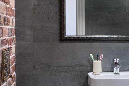 Loft-style bathroom interior details. Neutral gray porcelain stoneware, brick wall and mirror above the sink, stylish bathroom interior. Personal hygiene items Stock fotó