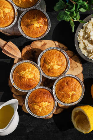 Freshly baked lemon muffins on a black wooden table. Homemade delicious magdalena, proofing after baking, ingredients on the table nearby, top view with copy space