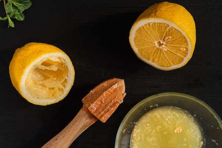 Lemon halves on a black wooden table, making lemon juice with a manual juicer, top view