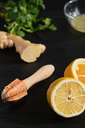 Lemon halves on a black wooden table, making lemon juice using a manual baking juicer, close-up, selective focus