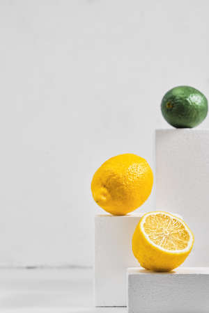 Fresh lemons and limes on a gray table, minimalistic concept with citrus fruits. Close-up, selective focus. Geometric texture background with copy space Stock fotó