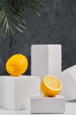 Lemons on gray neutral background, minimalist concept with lemons. Close-up, selective focus. Geometric forms, background with copy space