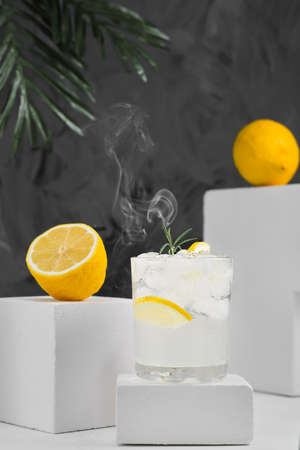 Lemonade or cocktail with lemon, ice, tonic and rosemary on gray neutral background, minimalist concept. Close up, selective focus on summer tonic detox drink, smoke rises above glass with drink
