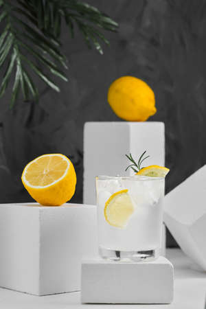 Lemonade with ice and lemon wedges in a glass on a gray neutral background, minimalist concept. Close-up, selective focus on a summer soft drink. Geometric shapes, background with copy space Stock fotó