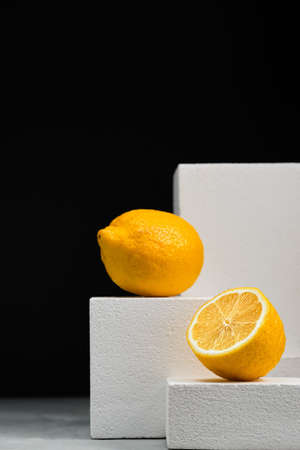 Lemons on dark background, minimalist concept with lemons. Close-up, selective focus. Geometric texture, background with copy space