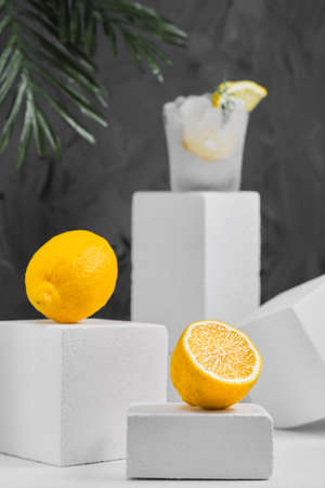 Lemons and lemonade glass on gray neutral background, minimalist concept with lemons. Close-up, selective focus. Geometric forms, background with copy space