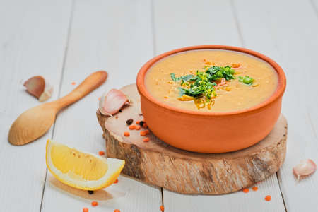 Red lentil soup with ingredients on a wooden white plate, close-up, selective focus. Traditional Turkish or Arabic lentil vegetable spicy soup. Healthy Middle Eastern Vegan Food