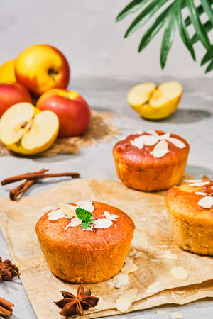 Delicious apple muffins with cinnamon with apples and almond flakes decorated with mint leaves, close-up, selective focus, vertical frame. Tea time or breakfast time, homemade cakes Stock fotó