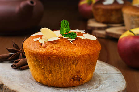 Delicious apple muffin with cinnamon with apples and almond flakes decorated with a mint leaf, close-up, selective focus. Tea time or breakfast time, homemade cakes