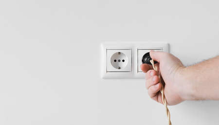 Male hand plugs a vintage electrical plug into a European outlet located on a white plaster wall, a copy of the space. Close-up of an electrical outlet