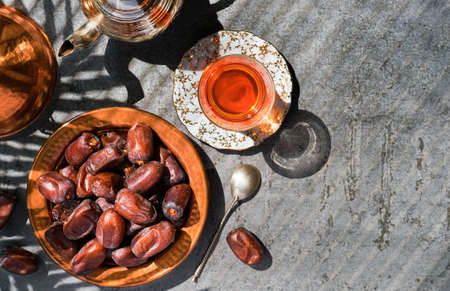 Dates on copper plate, next to red tea in glass of armudu and teapot. Layout of sweet date fruits on stone background, bright sunlight, shadows from palm leaves on table, top view with copy space Stockfoto