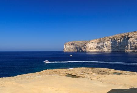 Malta. Gozo. Boat against rocks Stock Photo - 16597943