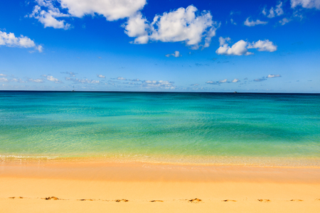 Idyllic afternoon at the beach in Barbados (Caribbean island): Nobody, white sand, clear turquoise water with waves and a sunny blue sky white clouds. Banque d'images