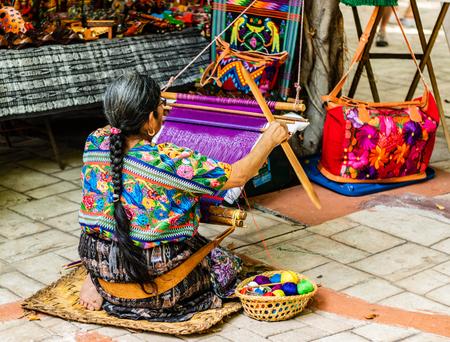 Mujer tejiendo en un antiguo pueblo de Guatemala. Vacilante tradicional de Guatemala.