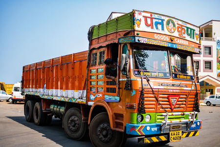 Gos, India - 2019. Colorful cargo truck under a summer blue sky with rich decorative paintings, typical for the trucks in India. Editorial