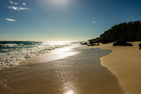Paradise travel destination beach in Hamilton, Bermuda. Elbow Beach with golden sand and a beautiful sunset.