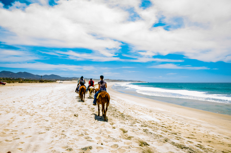 Cabo San Lucas, Mexico - Tourists horseback riding on the beach in Cabo San Lucas, Baja California.