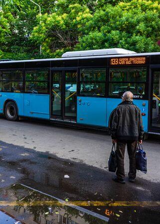 Bucarest, Roumanie - 2019. Vieil homme avec deux sacs à la gare routière. Éditoriale
