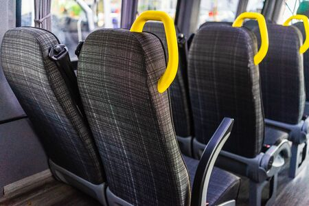 Empty seats with yellow handles in a minibus or van. 免版税图像