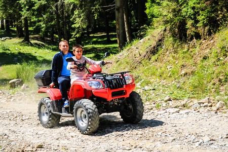 Iezer Mountains - Romania - 2019. Father and son having a fun ride in the forest of Iezer Mountains on a ATV.