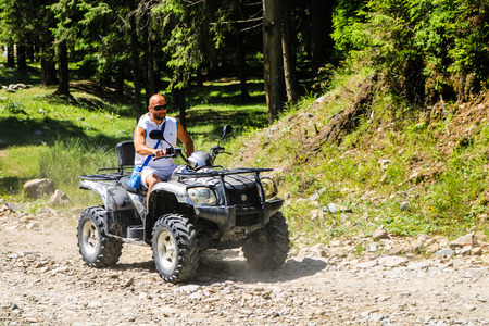 Iezer Mountains - Romania - 2019. Young people having a fun ride in the forest of Iezer Mountains on a ATV. Redakční