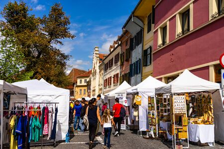 Sibiu, Romania - 2019. Tourists looking for souvenirs at local artisans shops in downtown Sibiu. Editorial