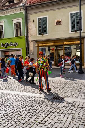 Sibiu, Romania - 2019. Man wearing colorful clothes and blowing up balloons for entertainment of people in the old town.