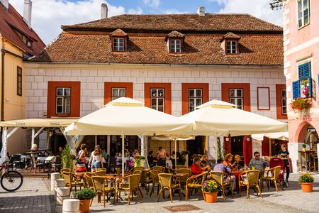Sibiu, Romania - 2019. People and tourists having lunch and wandering on the streets of Sibiu old town. Редакционное