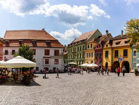 Sighisoara, Romania - 2019. People having lunch and wandering on the streets of Sighisoara old town. Редакционное