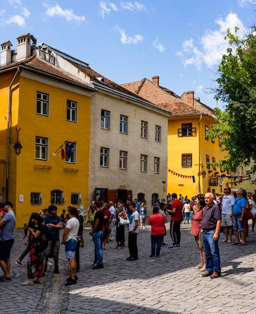 Sighisoara, Romania - 2019. People wandering on the streets of Sighisoara citadel (old town). Streets with colorful houses.
