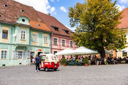 Sighisoara, Romania - 2019. People having lunch and wandering on the streets of Sighisoara old town near a tuk tuk car.