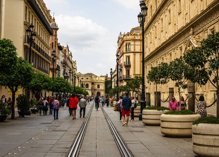 Seville, Spain – 2019. People walking down a street in the old city. Seville is the capital of Andalusia.