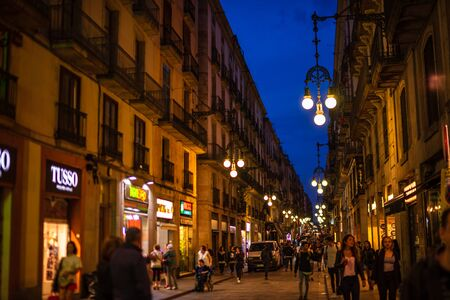 Barcelona, Spain – 2019. People walking on the old streets of Barcelona at night between local shops and tapas bars.