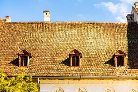 Medieval house in Sibiu with old roof tiles and old paint.