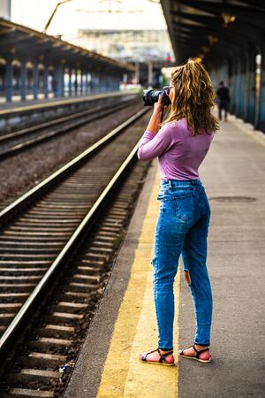 Young girl walking alone on train platform and taking photos on railway station