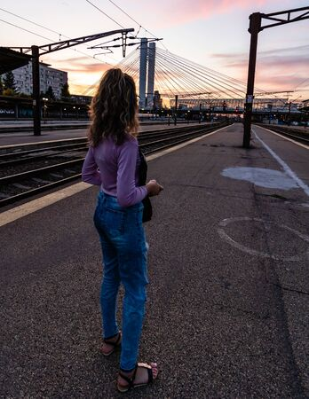 Young girl walking alone on train platform and taking photos on railway station Foto de archivo - 129990733