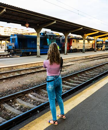 Young girl walking alone on train platform and taking photos on railway station Foto de archivo - 129990736