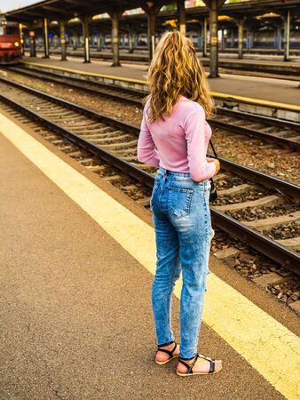 Young girl walking alone on train platform and taking photos on railway station Foto de archivo - 129990747